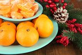Ripe tangerines in bowl with fir branch close up