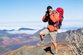 Photographer taking pictures outdoors on hiking trip. Outdoor nature photography.