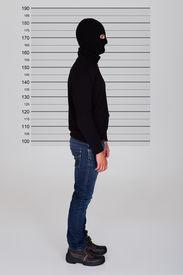 stock photo of lineup  - Burglar Wearing Balaclava Standing Against Police Lineup - JPG