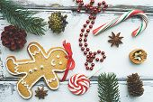 Composition of lollipop, sugar cane, ginger bread, beads, walnut, anise, some cones and conifer on white wooden background
