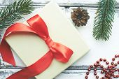 Composition of red beads, pine cone, conifer and xmas card with silk bow