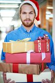 Young man in Santa cap holding heap of giftboxes