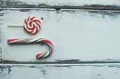 Sweet lollipop and sugar cane on white wooden background