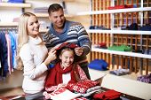 Portrait of young parents trying cap on their daughter in department store