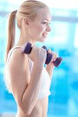 Attractive blond girl lifting barbells in gym
