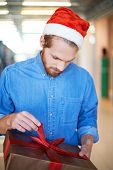 Guy in Santa cap unpacking Christmas present
