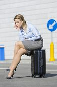 Full length of exhausted businesswoman sitting on luggage