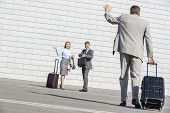 stock photo of carry-on luggage  - Rear view of businessman carrying luggage waving hand to colleagues - JPG