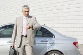 Businessman checking the time in front of car outdoors