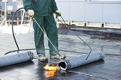 Roofer installing Roofing felt with heating and melting of bitumen roll by torch on flame during roo