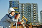 Surveyor builder worker with theodolite transit equipment at construction site outdoors during surveying work