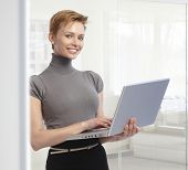 Young attractive elegant caucasian businesswoman standing with laptop computer at office. Working, looking at camera, toothy smile.  .