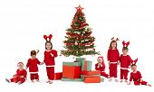 Cute kids in red with christmas tree and presents, isolated on white. Group, smiling, laughing, having fun, looking at camera.