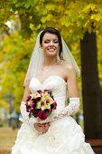 Portrait of a beautiful smiling bride in autumn park
