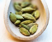 Whole cardamom in wooden spoon