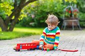 Cute Blond Kid Boy Playing With Red School Bus And Toys