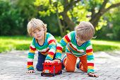 Two Little Kids Playing With Red School Bus