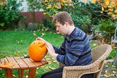 Young Man Making Halloween Pumpkin