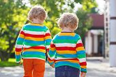 Two Little Sibling Children In Colorful Clothing Walking Hand In Hand