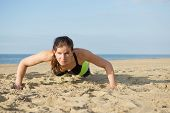 Woman doing push ups on a beach on a warm summer evening.