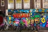 AMSTERDAM - AUGUST 29: Lots of bikes parked in front of a building painted with graffiti on August 2