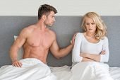 Not in Good Terms Young Couple on Bed with White Cover with Gray Wall Background.