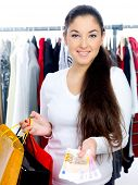 Smiling young woman happy from shopping with money left in her hand