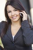 Beautiful happy young Latina Hispanic woman or businesswoman smiling and talking on her cell phone outside