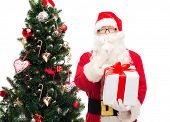 christmas, holidays and people concept - man in costume of santa claus with gift box and tree making hush gesture