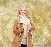 winter holidays, christmas, fashion and people concept - smiling young woman in winter clothes over yellow lights background