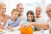 family, happiness, generation, holidays and people concept - happy family making halloween pumpkins