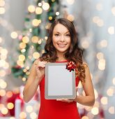 holidays, technology and people concept - smiling woman in red dress with tablet pc computer over christmas tree lights background
