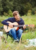 adventure, travel, tourism and people concept - smiling man with guitar and cooking food on bonfire in camping