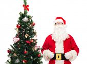 holidays and people concept concept - man in costume of santa claus with christmas tree