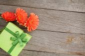 Orange gerbera flowers and gift box on wooden table background with copy space