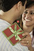 Hispanic couple hugging with gift