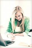 picture of smiling student girl writing in notebook