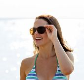 sea, summer vacation, holidays and people concept - smiling teenage girl in sunglasses
