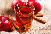 foto of sackcloth  - Apple cider with cinnamon sticks and fresh apples on sackcloth background - JPG