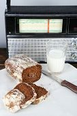 Rye bread and glass of milk on white fabric napkin on wooden table on radio set and light wall background