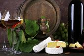 Wine in bottle and in goblet, Camembert cheese, grapes and wooden barrel on wooden table on wooden background