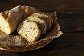 Sliced white bread on sackcloth napkin on wicker basket on wooden background