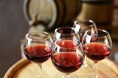 foto of tumblers  - Glasses of wine in cellar with old barrels  - JPG