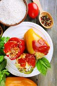 Composition with prepared stuffed peppers on plate and fresh herbs, spices and vegetables, on wooden