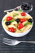 Pasta with tomatoes, olives and basil leaves in bowl on dark fabric background