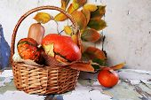 Pumpkins in wicker basket and leaves on old board on wall background