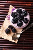 Healthy breakfast - yogurt with  blackberries and muesli served in glass jar, on dark  background