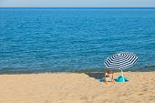 beach umbrella and chair  in front of the blue sea in a sunny day