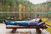 Young Male Hiker Resting Near Lake In Autumn Forest