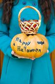 Young girl holding Halloween pumpkin and basket with candies, close-up, outdoors